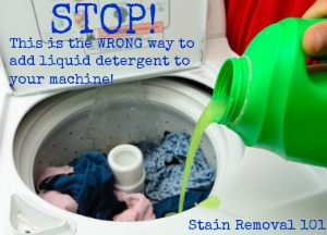pouring liquid laundry detergent the wrong way, with clothes already in machine